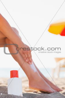 Bottle of sun block and female applying creme on leg on beach