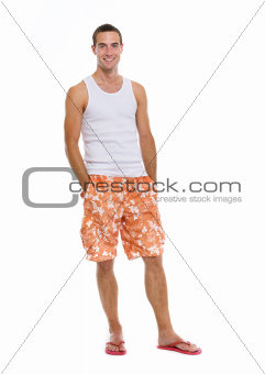 Full length portrait of on vacation smiling young man in shorts