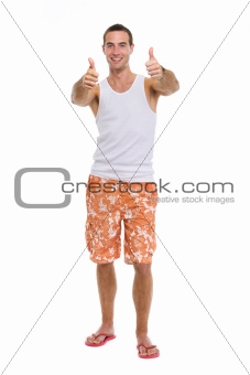 Full length portrait of resting on vacation smiling young guy showing thumbs up