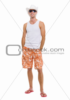Portrait of on vacation smiling young man in sunglasses and holiday hat