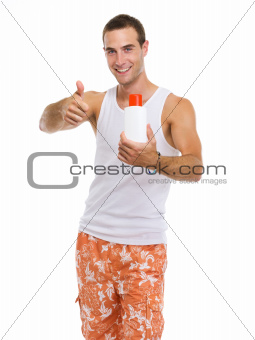 Happy young guy showing sun screen creme and thumbs up