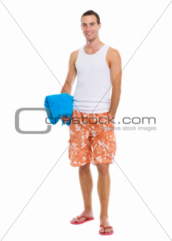 Happy resting on vacation young guy holding blue towel