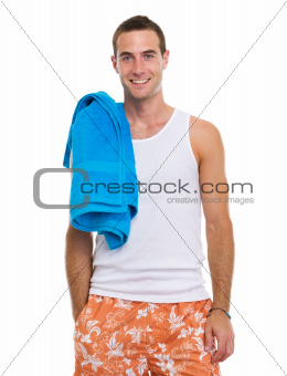 Smiling resting on vacation young guy with blue towel