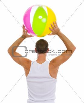 Man throwing beach ball. Rear view