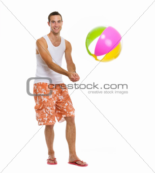 On vacation happy young man playing volleyball with beach ball