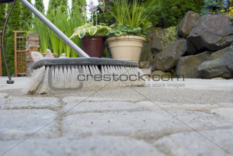 Broom Sweeping Sand into Pavers Low View