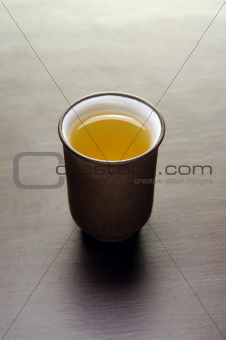 one chinese tea cup on wooden table with tea