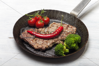 grilled steak in an iron pan