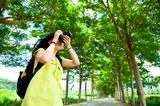 Young woman with backpack standing in the green forest taking photo