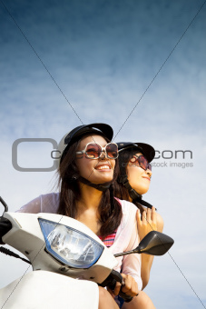 young woman riding scooter on the sunny day