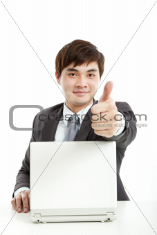 successful businessman working with computer and showing thumb up