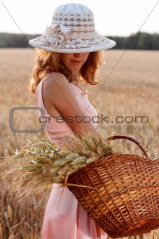 Elegant romantic woman in hat with basket in the wheat field