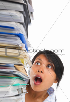 Asian lady surprised by high pile of paperwork