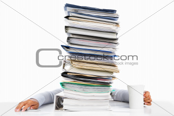 Sleeping worker behing high pile of paperwork