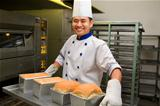 Baker holding fresh bread from oven