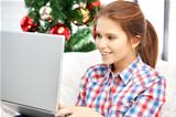 happy woman with laptop and christmas tree
