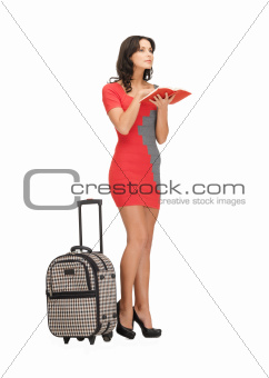 pensive woman with suitcase and book