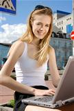 woman with laptop in a hi-tech urban surrounding