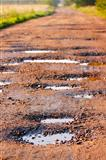 Red clay road with holes