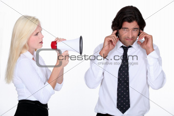 woman talking through a megaphone and a man plugging his ears