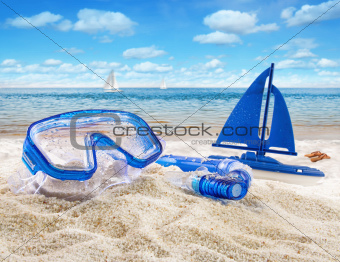 Goggles and toy sailboat in sand