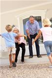 Grandparents Welcoming Grandchildren On Visit To Home
