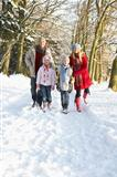 Family Walking Through Snowy Woodland