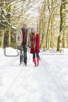 Couple Walking Through Snowy Woodland