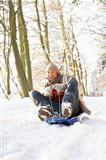 Man Sledging Through Snowy Woodland