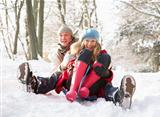 Couple Sledging Through Snowy Woodland