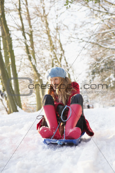 Woman Sledging Through Snowy Woodland