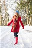 Woman Walking Through Snowy Woodland