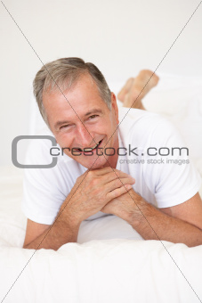 Senior Man Relaxing On Bed
