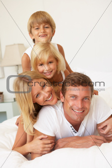 Portrait Of Young Family Relaxing In Bed Together