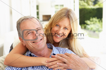 Portrait Of Father And Adult Daughter Relaxing On Sofa