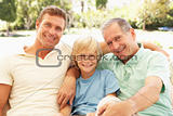 Portrait Of Grandfather, Son And Grandson Relaxing On Sofa