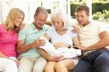 Extended Family Relaxing Together On Sofa With Newborn Baby