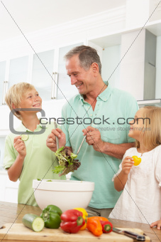 Grandchildren Helping Grandfather To Prepare Salad In Modern Kitchen