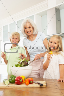 Grandchildren Helping Grandmother To Prepare Salad In Modern Kitchen