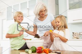 Grandchildren Helping Grandmother To Prepare Salad In Modern Kitchen