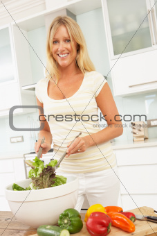 Woman Preparing Salad In Modern Kitchen