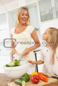 Mother & Daughter Preparing Salad In Modern Kitchen