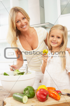 Mother & Daughter Preparing Salad In Modern Kitchen