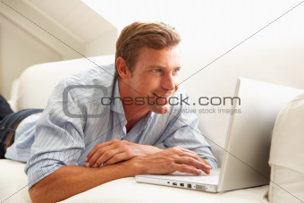Man Using Laptop Relaxing Sitting On Sofa At Home