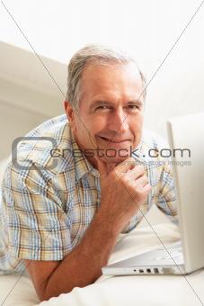 Senior Man Using Laptop Relaxing Sitting On Sofa At Home