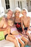 Portrait Of Grandparents With Grandchildren Sitting Together By Swimming Pool