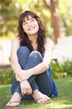 Portrait Of  Teenage Girl Sitting In Park