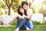 Portrait Of  Romantic Teenage Couple Sitting In Park