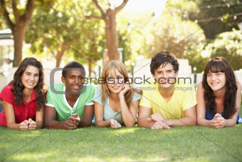 Group Of Teenagers Lying On Stomachs In Park