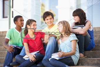 Group Of Teenage Friends Sitting On College Steps Outside